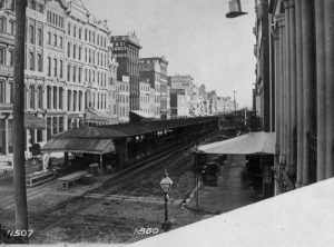 A black and white photograph of sheds running down the median in Market Street. Streetcar tracks are visible on either side.