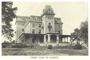 Photograph of the Ogontz Mansion, a massive, five story victorian home with a large wrap around porch and intricate masonry work. A large lawn leads up to the property.