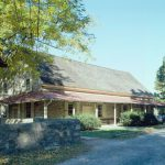 Color photogrpah of the Plymouth Friends Meeting House, a simple two and a half story a-frame stone and brick building. A low, stone wall sits to the east of the property and the foreground of the image is the parking lot, which is gravel and has a few cars in it.