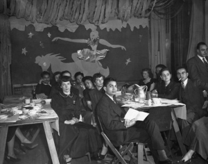 a black and white photograph of a group of students seated around a dining table