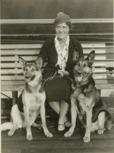 a black and white photograph of a woman flanked by two German Shepherd Dogs