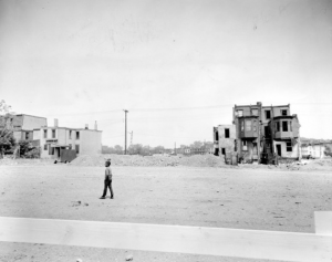 A black and white photograph of a young man walking on a desolate stretch of sidewalk. Behind him two small clusters of dilapidated row homes stand. The rest of the block has been razed.