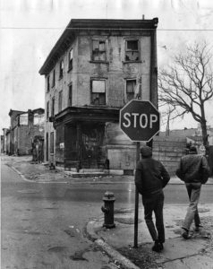 A black and white photograph of two men standing on a street corner. One leans on a stop sign. Across the street is a boarded up, graffitied row house, a dead tree, and scattered litter and debris.