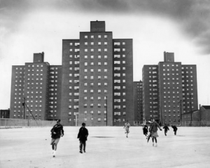 a black and white photograph of a small group of children playing in an empty, paved lot. Behind them, a group of three identical high rise housing project towers looms somewhat ominously.
