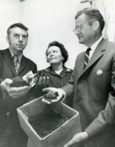 a black and white photograph of Ruth Patrick flanked by two unidentified men. The man on the right is holding a cardboard box of soil. All three people are holding soil samples in their outstretched hands and are wearing buttons with Earth Day logos on them.