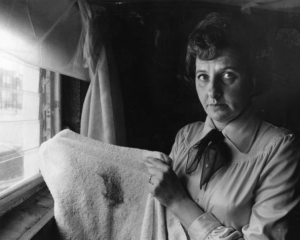 a black and white photograph of a woman standing in front of a window. She is looking direcltly into the camera and holding up a white towel with a large black soot mark on it.