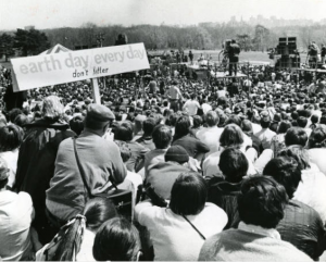 "a black and white photograph of a large crowd seated in front of a stage. The stage has several stacks of amplifiers. Crew members are working on the stage. In the foreground, a man holds a sign reading ""earth day every day. Don't litter."""