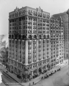 A black and white photograph of the Betz Building, a fourteen story stone building standing on the corner of Center Square.