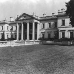 A black and white photograph of a Greek-Revival mansion with a columned portico