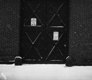 A black and white photograph of a building with a zoning notice to become a branch of Philadelphia's public library.