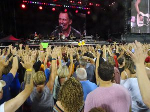 Photo of crowd near stage watching Bruce Springsteen perform.