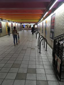 Photograph of people walking in concourse with closed umbrellas