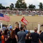 Cowtown Rodeo ring with audience in foreground and background and flag bearing horse riders in between.