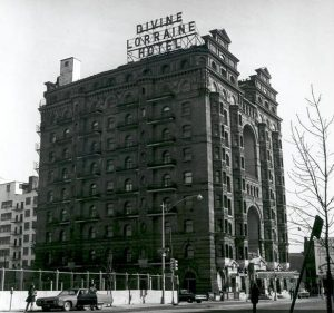 A black and white photograph of the Divine Lorraine Hotel. The building is ten stories tall. A sign on top of the building announces the hotel's name.