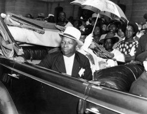 Father Divine, an African-American man wearing a pinstripe suit and hat, sits in an automobile. He is surrounded by people who are all hoping to catch a glimpse of him during his visit to Philadelphia. His wife Penninah is seated next to him and carries a parasol.