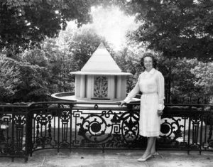 Mother Divine is shown next to a pyramid-shaped memorial at Father Divine's burial site. She is wearing a white dress and has her hand resting on a fence that serves as a barrier between her and the memorial.
