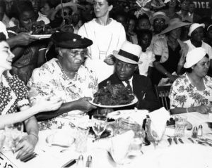 Father Divine, wearing a black suit and white hat, sits next to his wife Penninah, who wears a floral-print dress. They are seated at a large table at Shibe Baseball Park in Philadelphia. Penninah passes a plate of food to Father Divine while other guests enjoy the meal in the background.