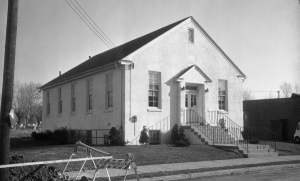A black and white photograph of a small, single-story church. It is painted white and is surrounded by a few trees.