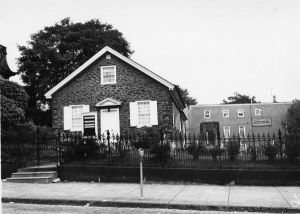 A black and white photograph of a single-story stone meetinghouse. It is surrounded by a black fence and there is a two-story building behind it.