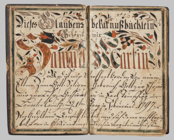 A color photograph of a booklet from 1790. The pages are yellowed with age but the calligraphy is still visible. The title is handwritten in shades of orange and green, and the subsequent text is detailed in cursive.