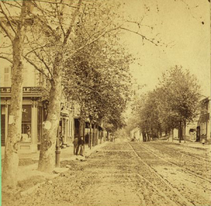 A black and white photograph with a yellow tint that depicts a quiet Main Street. A few buildings are visible in the background, as well as two men standing by a tree and having a conversation. The streets are clear.