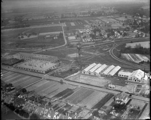 This black and white photograph shows a large factory surrounded by houses and open plains. A water tower sits in the middle of the property and several can production buildings sit on both sides.