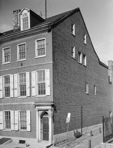This black and white photograph shows a three story house on Locust Street in Philadelphia. It is made of brick and has eight windows on the front as well as seven on the side.