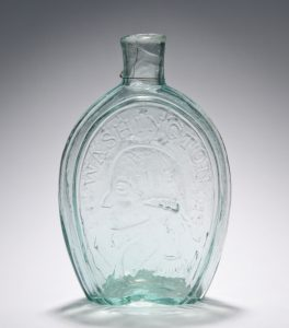 "This photograph shows a glass flask made at the Bridgeton Glass Works. A profile of George Washington is engraved on the front and surrounded by text that reads ""Washington."""