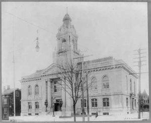 This black and white photograph shows a large courthouse with large glass windows and a central tower. It is surrounded by utlity poles and lights.