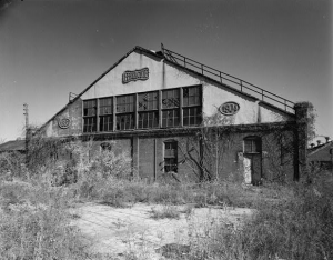 This black and white photograph shows a deteriorated machine production facility. It has a long, narrow roof and several windows are broken. Weeds cover the pavement in the foreground.