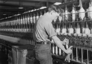 This black and white photograph shows a worker fixing spinning machines in a textile factory. His sleeves are rolled up as he replaces large spools of thread.