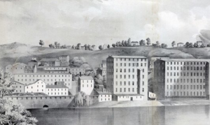 This black and white photograph shows a group of large factories bordering a river. A few houses and trees are visible on hills in the background. One of the factories has an opening in the middle that spills into the river.