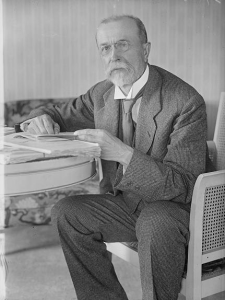This black and white photograph depicts Tomáš Garrigue Masaryk, an independence leader for Czechoslovakia. He is wearing a plaid suit and sitting at a table.