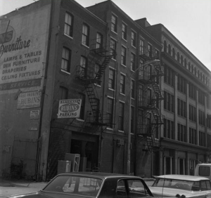 This black and white photograph shows the Wireworks building on Race Street in Philadelphia. An advertisement for a furniture store can be seen on the side of the building and a few 1970s cars sit in the foreground.