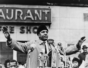 This black and white photograph shows Bayard Rustin, a civil rights activist, as he addresses as crowd in New York City. Rustin's arms are raised and there are several microphones for TV and radio stations on the podium in front of him.