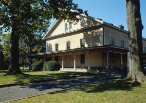 This color photograph depicts the Germantown Friends Meeting House. The building has a tan-yellow paint color, a long secondary roof that runs above the first floor, and a few windows at symmetrical points on all three floors.