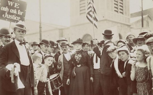 This black and white photograph shows labor activist Mother Jones surrounded by a large group of child textile workers and their parents.