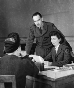 This black and white photograph shows a man and woman in American Friends Service Committee uniforms talking to a woman seated at a table. The uniformed woman writes notes while the uniformed man looks at the camera.