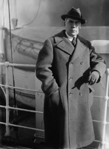 This black and white photograph shows Albert C. Barnes on the deck of a boat. He wears a large winter coat, gloves and hat and leans against the railing. Two smaller boats can be seen in the background.