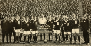 "This black and white photograph shows the members of the Bethlehem Football Club after their victory over the Brooklyn Celtic Football Club in a 1914-15 soccer championship. The men wear uniforms with a large letter ""B"" sewn onto the front. The stadium seats behind them are filled with spectators."