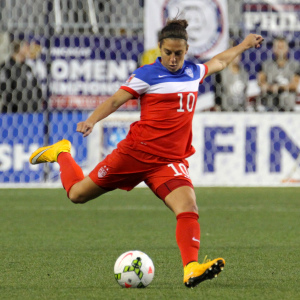 This color photograph shows Carli Lloyd, an Olympic gold medalist and FIFA World Champion. Lloyd, dressed in a red, white and blue uniform, is captured in motion here as she prepares to kick a soccer ball that rests in front of her.