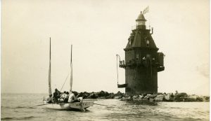This black and white photograph shows a lighthouse surrounded by rocks in the middle of the Delaware Bay. A small boat with five men in it can be seen in the foreground.