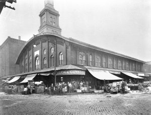 This black and white photograph shows a fish market in Philadelphia. Large awnings cover barrels and buckets full of merchandise. A few workers pose beneath the main entrance.