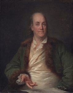 This is a painting of Benjamin Franklin, gesturing towards a piece of paper sitting on a desk next to a pair of bifocals. He is wearing a green, fur-lined jacket.