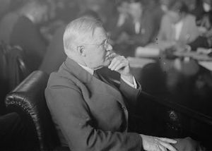 This black and white photograph shows Joseph R. Grundy in a board meeting. The other board members are in the background while the camera focuses on Grundy.