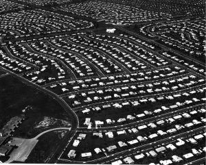This aerial black and white photograph shows several hundred houses aligned in straight rows in Levittown, Pennsylvania.