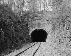 This black and white photograph shows a tunnel connected to a section of railroad track. The area is surrounded by trees and rocks.