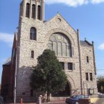 This color photograph shows the Mother Bethel AME Church. A large stained glass window appears near the top and the outer later is comprised of layered stone.