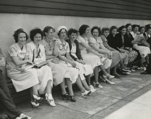 This black and white photograph shows a group of fourteen women seated on a bench outside the Apex Hosiery factory as they prepare for a strike.