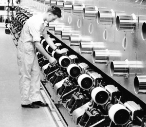 This black and white photograph shows a worker adjusting the threads of a large nylon machine. There are several large round spools close to him leading to a polished steel structure above.